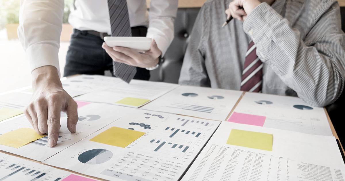 två affärsmän tittar på dokument med stapel - och cirkeldiagram